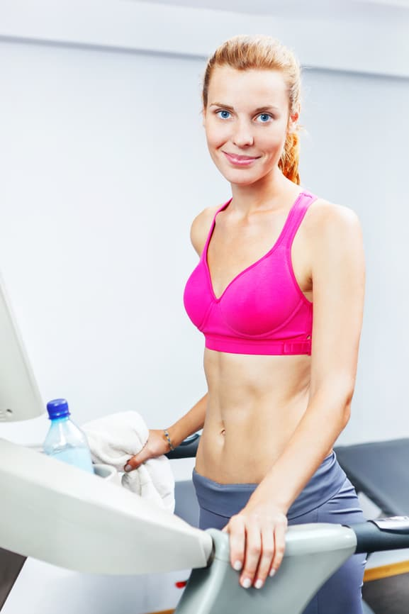 Young woman doing cardio on treadmill in a gym.
